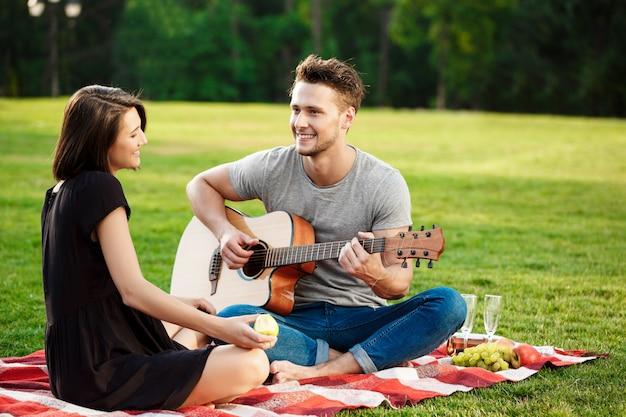 公園で休んで若い美しいカップル