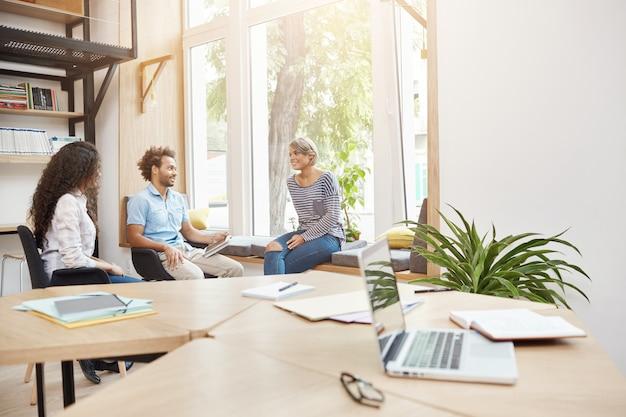 Группа из трех молодых предпринимателей, работающих вместе над исследованиями в светлой библиотеке, обсуждают идеи проекта, просматривают документацию, проводят продуктивное утро. бизнес-концепция