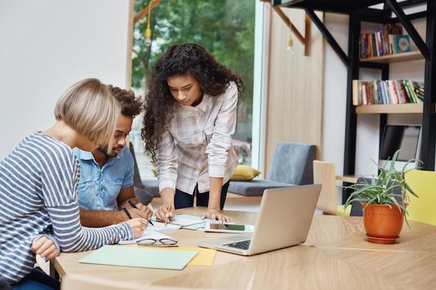 Команда творческих молодых предпринимателей работает над командным проектом, просматривает информацию о прибыли на ноутбуке, пишет идеи на бумаге. концепция мозгового штурма.