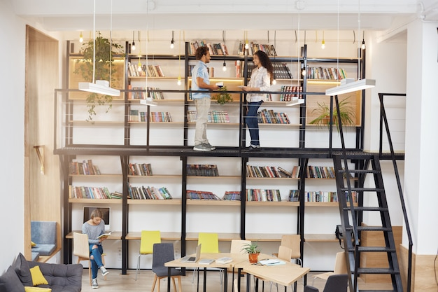 Большая современная библиотека с минималистичным дизайном, компьютеры, удобные кресла, второй этаж с книжными полками. утро в уютном тихом месте. люди проводят время в университетской библиотеке.