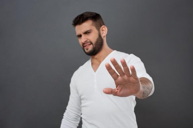 不快な男は拒否し、灰色の壁に手を伸ばします