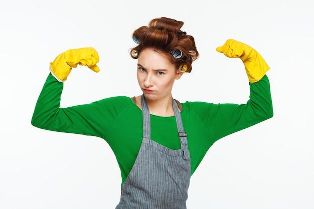 Хорошенькая молодая домохозяйка показывает силу позирует и высмеивать