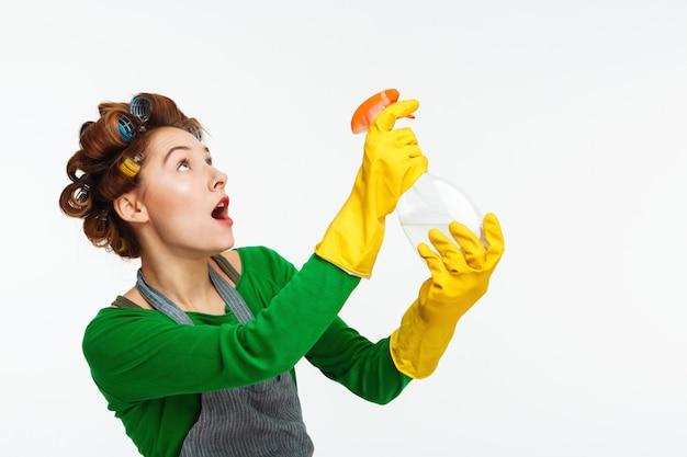 若い女性は家のポーズを掃除しながらスプレーを使用します