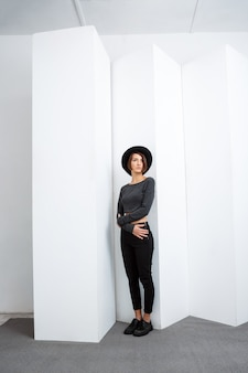Молодая красивая девушка в черной шляпе позирует на белой стене