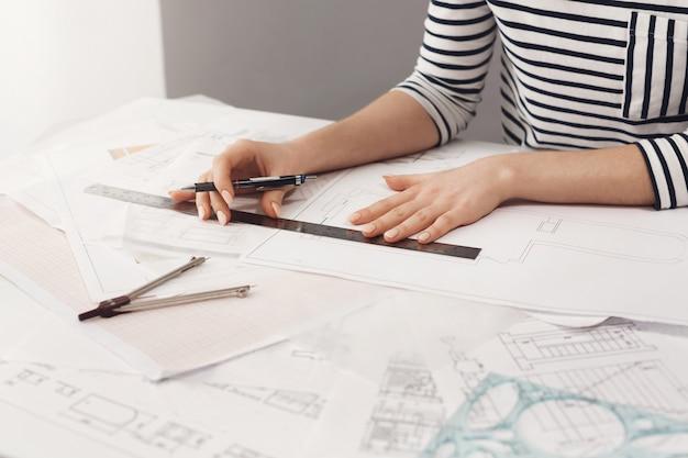 ストライプシャツの机に座って、ペンと定規を手に持って、青写真を作って、自宅で新しいプロジェクトに取り組んでいる美しい若い女性建築家の詳細を閉じます。ビジネスとアート