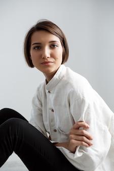 Сидеть молодой красивой девушки усмехаясь на поле над белой стеной.