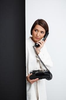 Девушка говорит по старому телефону на черно-белой стене