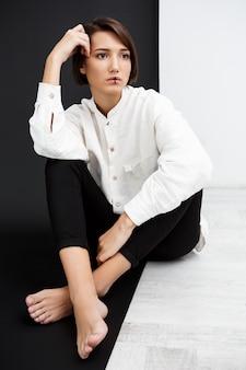 黒と白の壁の上の床に座って美しい少女