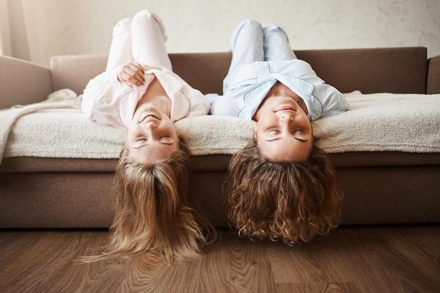 Девчонки хотят просто повеселиться. красивые подружки лежат на диване вверх ногами с прикасаясь к полу, носят уютные пижамы, улыбаются и отдыхают с закрытыми глазами, прекрасно проводят время вместе.