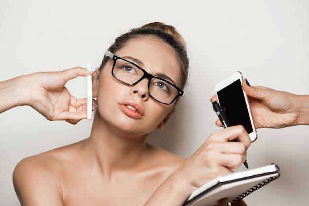 ノートを保持している若い美しい女性実業家に電話を与える手