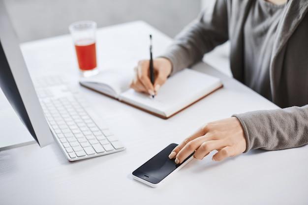 Обрезанный снимок руки записи вниз в блокнот и трогательно смартфон. сотрудник работает в офисе, проверяет почту через компьютер и пьет свежий сок для повышения энергии. сроки близки