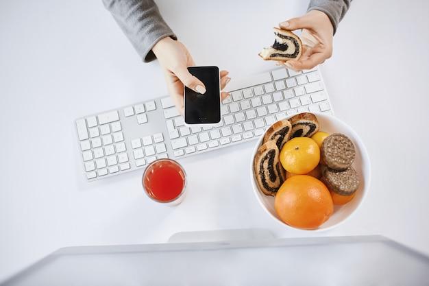 コンピューターの前で昼食をとり、丸めたケーキとスマートフォンを保持している女性のハイアングルショット。忙しい女性が仕事をしながら時間を無駄にしないで食べ、プロジェクトを時間内に終わらせ、新鮮なジュースを飲みながら楽しんでいます