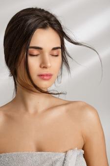 美しい女性は柔らかいタオルで覆われています。目を閉じて立っています。