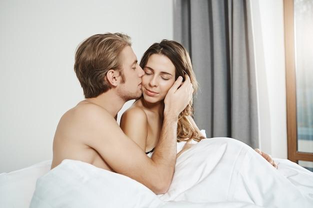 昼間一緒にベッドに横たわっている間、頬に魅力的な妻を優しくキスするハンサムな夫の肖像画。寝室に寄り添うカップル、周りをすべて忘れてしまったカップル