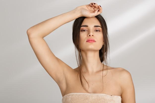 Великолепная женщина покрыта полотенцем. стоя с рукой на лбу.