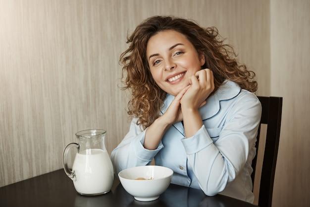 家族の輪で健康的な朝食。牛乳と一緒に穀物を食べながら手に寄りかかって巻き毛の美しい若い母親、幸せな笑顔、夫とのチャット