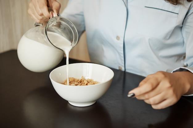 朝の簡単な朝食を準備するガールフレンド。高速で食べたいと服を着てオフィスに行くために穀物をボウルに牛乳を注ぐナイトウェアの女性のショットをトリミング