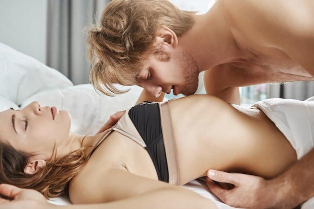 セクシーな魅力的なガールフレンドは、ハンサムな男とベッドで横になっているエロティックなランジェリーを着て、彼が朝の官能的な前戯の間に彼女に触れてキスしている間。寝室で性的に引き付けられるカップル