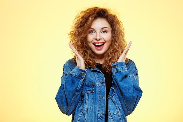 黄色の壁にカジュアルなストリートジーンズのジャケットで驚いて美しいブルネットの巻き毛の少女の笑顔のポートレートを閉じます