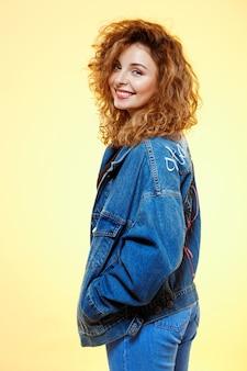 黄色の壁にカジュアルなストリートジーンズのジャケットで笑顔の美しいブルネットの巻き毛の少女の肖像画を間近します。