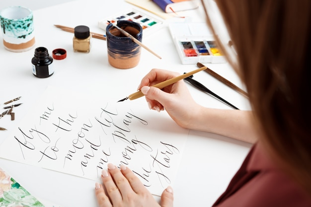 はがきに書道を書いている女の子。アートデザイン。