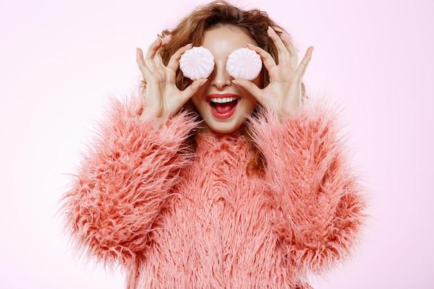 白い壁にマシュマロを保持しているピンクの毛皮のコートで陽気な笑顔の美しいブルネットの巻き毛の少女の肖像画を間近します。
