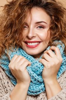 ニットのセーターとベージュの壁に灰色のネックウォーマーで陽気な笑顔の美しいブルネットの巻き毛の少女の肖像画を間近します。