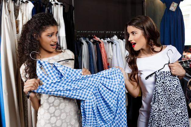 Красивая девушка, забирая платье от другого в торговом центре.