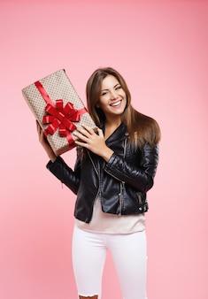 Молодая женщина в прохладном наряде, держа подарок на день рождения, глядя прямо