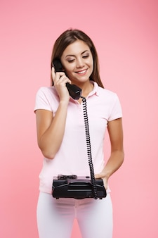 Очаровательная молодая женщина в светло-розовом поло и белых штанах