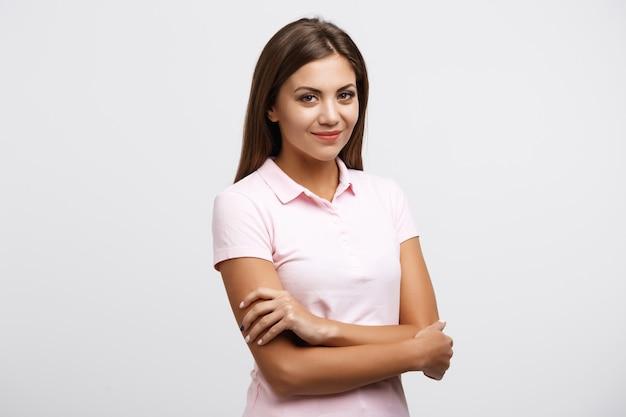 Молодая женщина в яркой рубашке позирует на белой стене