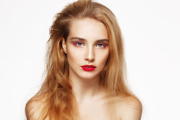 明るいメイクと美しい自信を持って少女のクローズアップの肖像画。白い壁。分離されました。美容コンセプト。