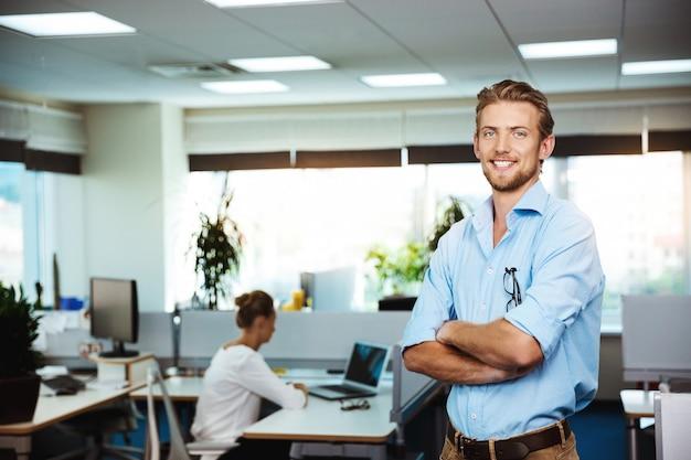Молодой успешный бизнесмен, улыбаясь, позирует со скрещенными руками, над офисом