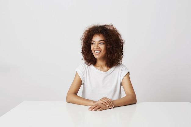 Красивая африканская девушка улыбается, смеясь сидя над белой стеной копирование пространства.