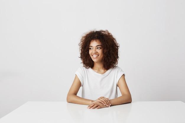 白い壁コピースペースの上に座って笑って笑って美しいアフリカの女の子。
