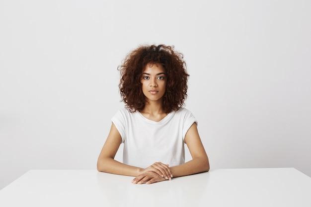 白い壁の上に座って美しいアフリカ少女の肖像画