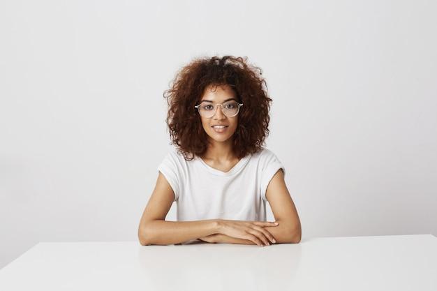 Молодая красивая африканская девушка в очках, улыбаясь, сидя над белой стеной