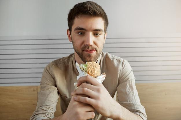 魅力的な黒髪の男がカフェに座って、サンドイッチで幸せそうな表情で見て、仕事で一日中何かを食べて幸せです。ハンバーガーを食べに行く空腹の男。