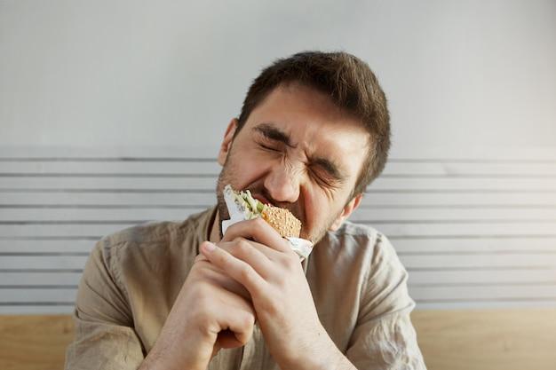 Молодой небритый красивый парень с темными волосами, ест бутерброд в фаст-фуд с закрытыми глазами, с счастливым и довольным выражением.