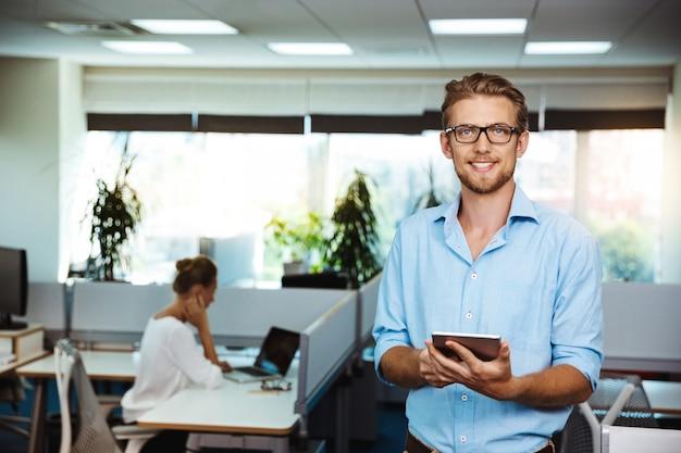 Молодой красивый успешный бизнесмен, улыбаясь, держа планшет, над офисом