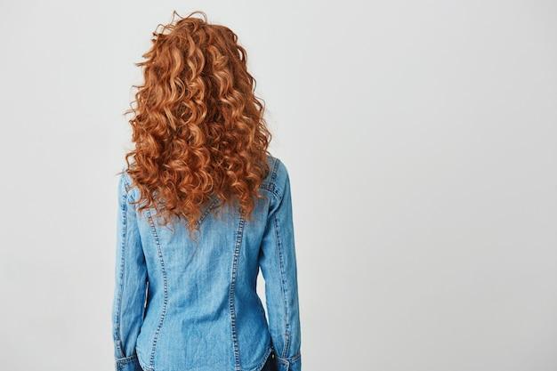 カメラに戻って立っている赤い巻き毛を持つ少女の写真。コピースペース。