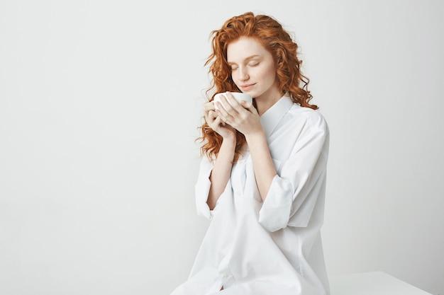 テーブルの上に座ってホールディングカップを笑顔のシャツで若い優しい赤毛の女の子目を閉じてください。