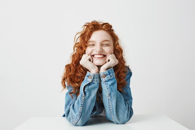 テーブルに座っている頬に手を喜んで笑って満足している赤毛の女の子。