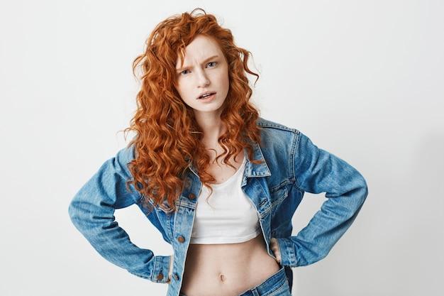 Грубая молодая девушка с рыжими вьющимися волосами жестоко с оружием подбоченясь.