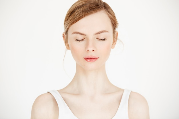 白い背景に分離された清潔でさわやかな肌を持つ美しい少女の肖像画。目を閉じた。美容と健康のライフスタイル。