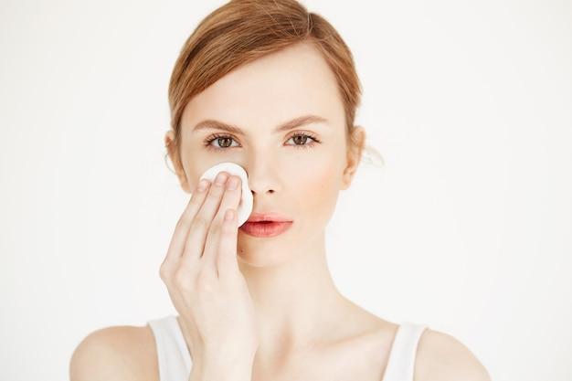 綿スポンジで顔を洗う美しい自然なブロンドの女の子。美容とスパ。