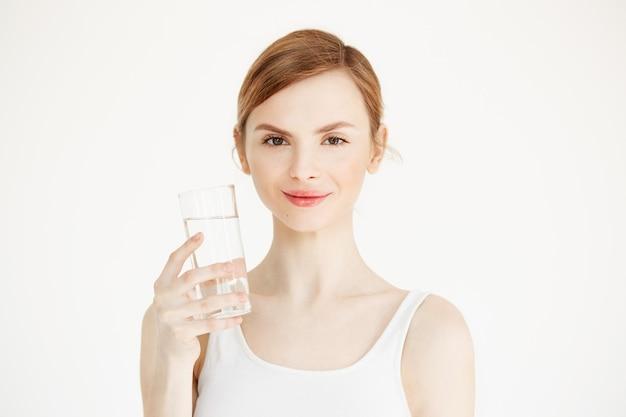水の持ち株のガラスを笑顔の完璧な肌を持つ美しい少女。美容と健康のライフスタイル。