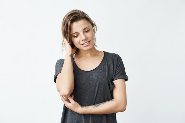 Застенчивая молодая красивая татуированная девушка улыбается, глядя вниз.