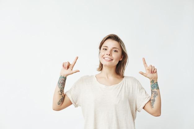 幸せな誠実な若い女の子が笑顔を指さします。