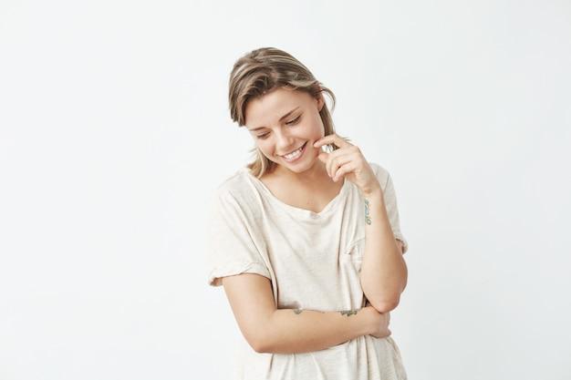 Портрет молодой красивой застенчивой девушки, улыбаясь, глядя вниз.